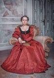 Härlig kvinna i medeltida klänning på fåtöljen Fotografering för Bildbyråer