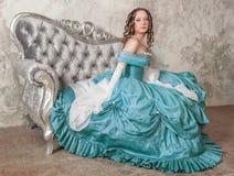 Härlig kvinna i medeltida klänning på soffan arkivfoto