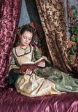 Härlig kvinna i medeltida klänningläsebok royaltyfria foton
