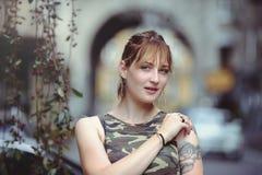 Härlig kvinna i militär klänning i stad och tatuering på händer arkivbilder