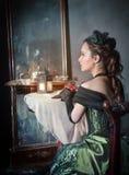 Härlig kvinna i near spegel för medeltida klänning arkivfoto