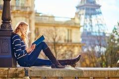 Härlig kvinna i Paris som läser en bok Royaltyfri Bild