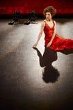 Härlig kvinna i röd kappa på etapp royaltyfri bild