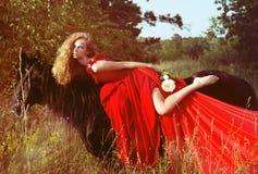 Härlig kvinna i röd klänning på den svarta hästen Royaltyfria Foton