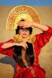 Härlig kvinna i röd klänning på sand Fotografering för Bildbyråer