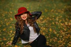 Härlig kvinna i rött hattsammanträde på gräset i parkera i höst Royaltyfria Foton