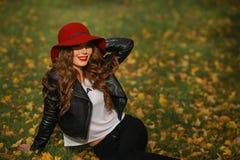 Härlig kvinna i rött hattsammanträde på gräset i parkera i höst Royaltyfria Bilder