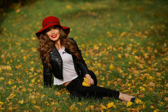 Härlig kvinna i rött hattsammanträde på gräset i parkera i höst Arkivfoto