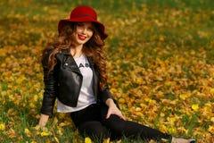 Härlig kvinna i rött hattsammanträde på gräset i parkera i höst Fotografering för Bildbyråer