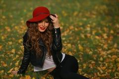 Härlig kvinna i rött hattsammanträde på gräset i parkera i höst Arkivbild
