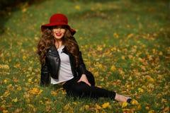 Härlig kvinna i rött hattsammanträde på gräset i parkera i höst Royaltyfri Fotografi