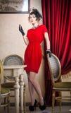 Härlig kvinna i rött med handskar och den idérika frisyren som poserar nära långa purpurfärgade gardiner Romantiskt mystiskt röka Arkivbild