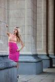 Härlig kvinna i rosa färgklänning bland kolonner Royaltyfri Fotografi