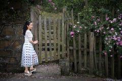 Härlig kvinna i rosträdgård Arkivfoto