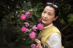 Härlig kvinna i rosträdgård Arkivfoton