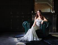 Härlig kvinna i sammanträde för aftonklänning på en läderfåtölj i en lyxig inre Arkivbilder