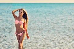 Härlig kvinna i sexig bikini som kopplar av på sommarstranden arkivbild