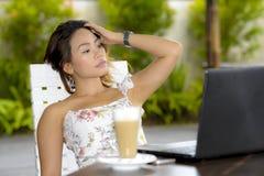 Härlig kvinna i sommarklänning utomhus på den trevliga coffee shop som har frukostnätverkande eller arbete med bärbar datordatore Royaltyfri Foto