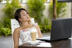 Härlig kvinna i sommarklänning utomhus på den trevliga coffee shop som har frukostnätverkande eller arbete med bärbar datordatore Royaltyfria Bilder