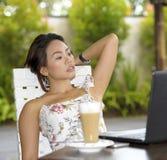 Härlig kvinna i sommarklänning utomhus på den trevliga coffee shop som har frukostnätverkande eller arbete med bärbar datordatore Arkivbild