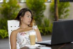 Härlig kvinna i sommarklänning utomhus på den trevliga coffee shop som har frukostnätverkande eller arbete med bärbar datordatore Royaltyfri Bild