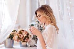 Härlig kvinna i sovrummet som dricker kaffe En flicka rymmer koppen, tycker om en drink fotografering för bildbyråer