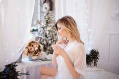 Härlig kvinna i sovrummet som dricker kaffe En flicka rymmer koppen, tycker om en drink royaltyfri fotografi