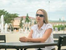 Härlig kvinna i stads- kafé på bakgrunden av den gamla staden Arkivfoto