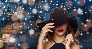 Härlig kvinna i svart hatt över nattstad Fotografering för Bildbyråer