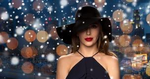 Härlig kvinna i svart hatt över nattstad Arkivbilder