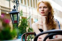 Härlig kvinna i svart klänning i kafé på sommardag royaltyfria foton