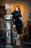 Härlig kvinna i svart klänningtappninglandskap Arkivfoto
