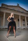 Härlig kvinna i svart posera för klänning som är utomhus-. Sexig kvinna i stilfull retro plats. Elegant kvinna framme av en slott. Royaltyfria Bilder