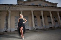 Härlig kvinna i svart posera för klänning som är utomhus-. Sexig kvinna i stilfull retro plats. Elegant kvinna framme av en slott. Royaltyfri Bild