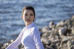 Härlig kvinna i traditionellt koppla av för Vietnam kultur på sjön bredvid blått vatten Arkivfoto