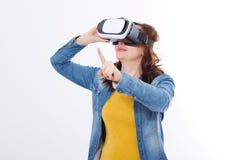 Härlig kvinna i vrexponeringsglas, rörande luft för skyddsglasögon vid fingret som isoleras på vit bakgrund Virtuell verklighetbe arkivfoto