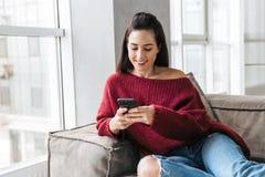 Härlig kvinna inomhus i hem på soffan genom att använda mobiltelefonen royaltyfri fotografi
