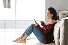 Härlig kvinna inomhus i hem på soffan genom att använda mobiltelefonen royaltyfria foton