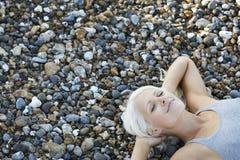 Härlig kvinna med ögon stängt ligga på kiselstenar på stranden Arkivfoton