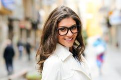 Härlig kvinna med ögonexponeringsglas som ler i stads- bakgrund fotografering för bildbyråer
