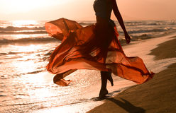 Härlig kvinna med att flyga den röda klänningen, strand Arkivbilder
