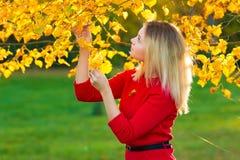Härlig kvinna med Autumn Leaves på nedgångnaturbakgrund Royaltyfri Foto