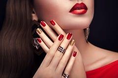 Härlig kvinna med bärande smycken för perfekt smink och för röd och guld- manikyr royaltyfri foto