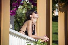 Härlig kvinna med baddräktsammanträde på en balkong med bougainvilleablomman arkivbild