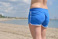 Härlig kvinna med blåa kortslutningar som tycker om se sikt av stranden Arkivfoton