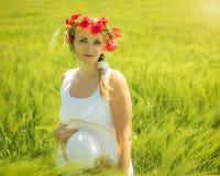 Härlig kvinna med blommavallmo på huvudet i ett fält av grön råg Arkivfoton