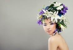 Härlig kvinna med blommor och modemakeup arkivfoton