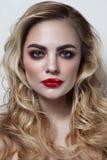Härlig kvinna med blont lockigt hår och röd läppstift Arkivfoto