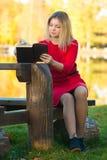 Härlig kvinna med boken på nedgångnaturbakgrund Royaltyfri Bild
