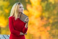 Härlig kvinna med boken på nedgångnaturbakgrund Arkivbilder